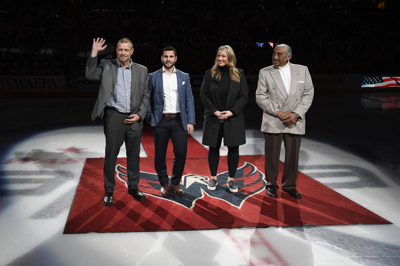 The 2019 U.S. Hockey Hall of Fame class, from left to right, Tim Thomas, Brian Gionta, Krissy Wendell and Neal Henderson stand on the ice before a ceremonial puck drop ahead of an NHL hockey game, Wednesday, Dec. 11, 2019, in Washington. (AP Photo/Nick Wass)