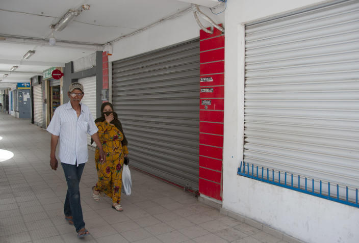 People walk past closed shops in La Marsa district,just outside Tunis, Monday, May, 10, 2021. Tunisia announced on Friday strict new measures to try to contain the spread of the coronavirus, with the prime minister saying that the health system risks collapsing if something is not done. Houses of prayer are being ordered closed starting Sunday for a week, along with outdoor markets and large stores and malls. Shops selling food can remain open. (AP Photo/Hassene Dridi)