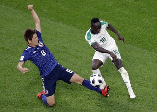 Japan's Genki Haraguchi, left, defends against Senegal's Sadio Mane during the group H match between Japan and Senegal at the 2018 soccer World Cup at the Yekaterinburg Arena in Yekaterinburg , Russia, Sunday, June 24, 2018. (AP Photo/Mark Baker )