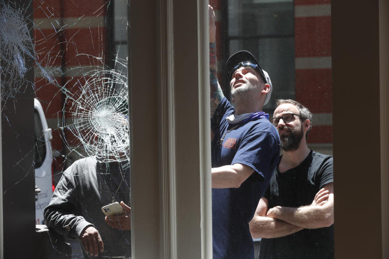 Nilas Porman, right, the manager of a Bang & Olufson store, watches as worker, center, describes how he will repair and protect the store's broken windows, Sunday, May 31, 2020, in New York. The windows were broken Saturday night during protests over the death of George Floyd, who died May 25 after he was pinned at the neck by a Minneapolis police officer. (AP Photo/Kathy Willens)