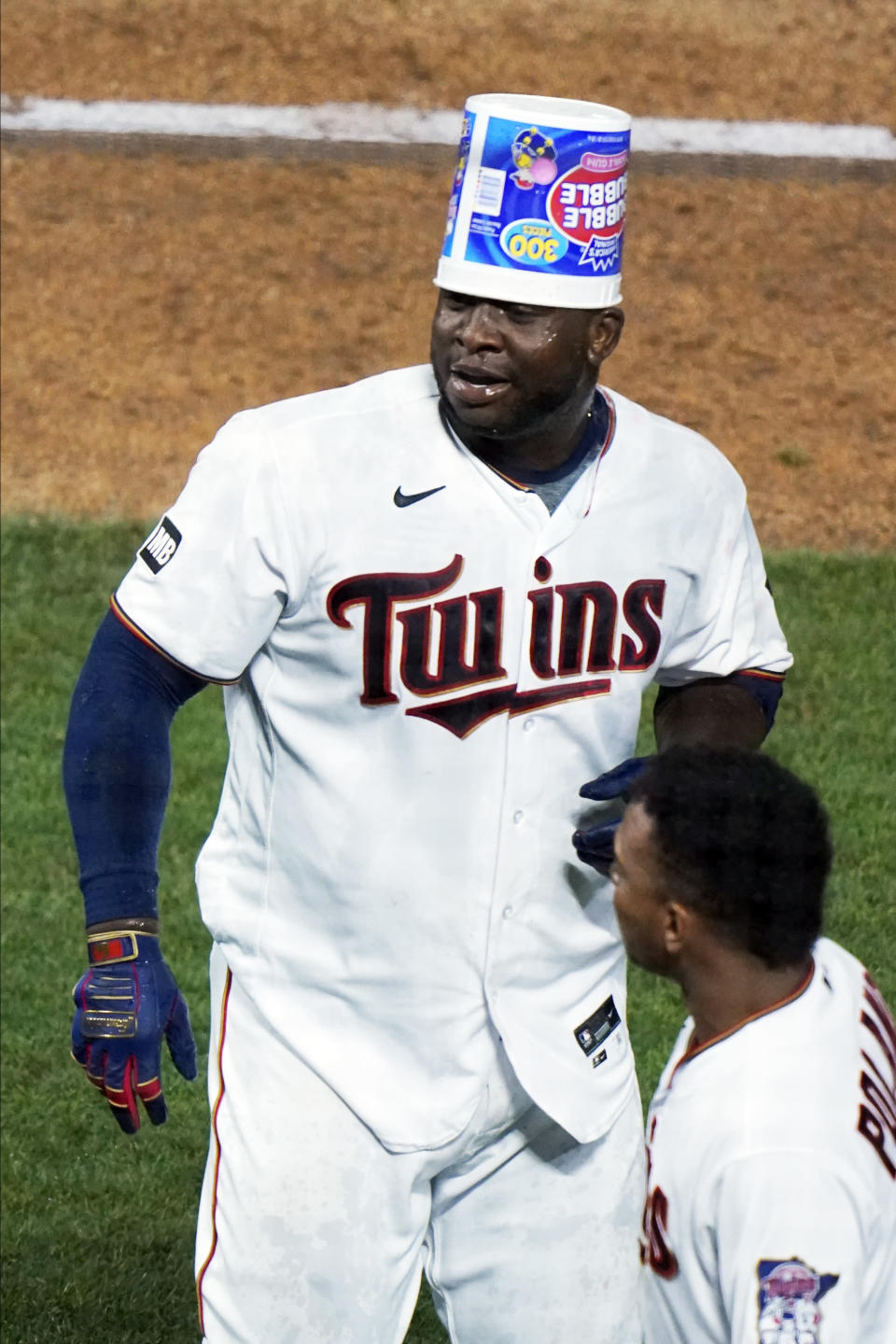 Minnesota Twins' Miguel Sano wears the bubble gum container on his head following his walk-off, two-run home run against the Cincinnati Reds in the 12th inning of a baseball game, early Tuesday, June 22, 2021, in Minneapolis. The Twins won 7-5. (AP Photo/Jim Mone)