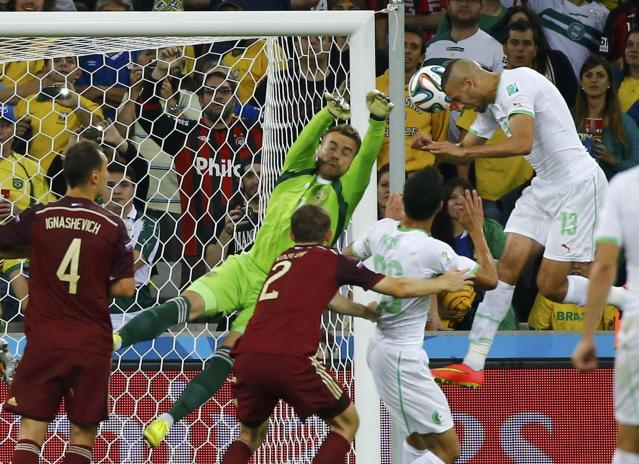 Algeria's Islam Slimani (R) heads the ball to score a goal against Russia during their 2014 World Cup Group H soccer match at the Baixada arena in Curitiba June 26, 2014. REUTERS/Damir Sagolj (BRAZIL - Tags: SOCCER SPORT WORLD CUP TPX IMAGES OF THE DAY)