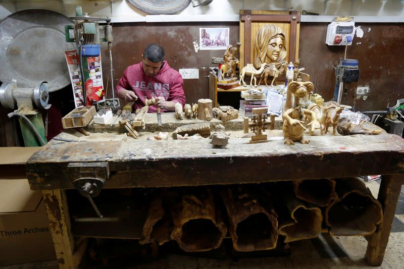 Palestinian worker carves figurines from olive wood to be sold during Christmas season, at a workshop in Bethlehem in the Israeli-occupied West Bank