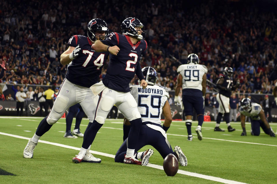 Houston Texans quarterback AJ McCarron (2) celebrates after scoring a touchdown as offensive guard Max Scharping (74) joins him while Tennessee Titans inside linebacker Wesley Woodyard (59) kneels at the goal line during the second half of an NFL football game Sunday, Dec. 29, 2019, in Houston. (AP Photo/Eric Christian Smith)
