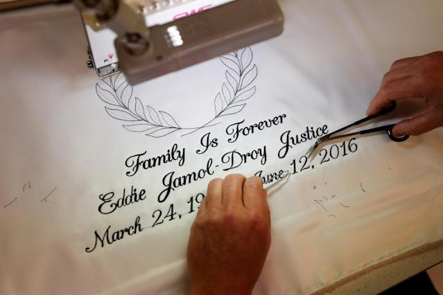 <p>A worker at Cardinal Casket Co. trims a piece of embroidery for a casket before the funeral of Pulse night club shooting victim Eddie Justice in Orlando, Florida, U.S., June 21, 2016. (REUTERS/Carlo Allegri) </p>