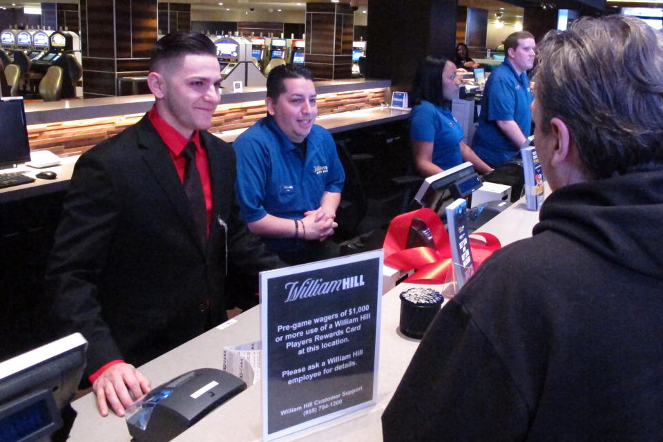 Customers make bets at the William Hill sportsbook inside the Tropicana casino in Atlantic City N.J., on March 8, 2019. Caesars Entertainment announced Wednesday, Sept. 30, 2020, it is buying William Hill for $3.7 billion. (AP Photo/Wayne Parry)