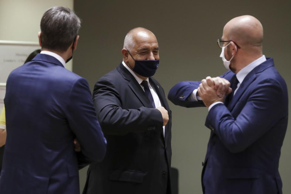 European Council President Charles Michel, right, greets Bulgaria's Prime Minister Boyko Borissov, center, with an elbow bump during a round table meeting at an EU summit in Brussels, Friday, July 17, 2020. Leaders from 27 European Union nations meet face-to-face on Friday for the first time since February, despite the dangers of the coronavirus pandemic, to assess an overall budget and recovery package spread over seven years estimated at some 1.75 trillion to 1.85 trillion euros. (Stephanie Lecocq, Pool Photo via AP)