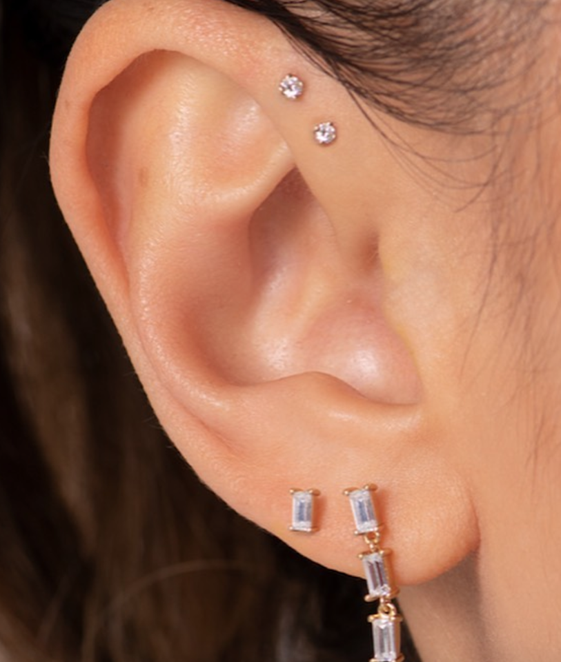 """This piercing looks great with hoops or studs, and you can either mix and match earrings or keep them identical depending on your vibe. However, the healing process for this one can be a little intense. """"The snakebite does require more care and attention, since two piercings close together can cause extra swelling,"""" says Bubbers. """"We recommend using saline and not sleeping on that side for a few weeks."""""""