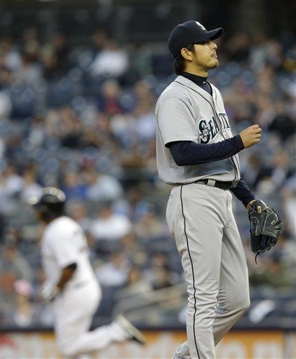 Seattle Mariners starting pitcher Hisashi Iwakuma, right, looks away as New York Yankees' Vernon Wells rounds the bases after hitting a home run during the first inning of a baseball game at Yankee Stadium in New York, Wednesday, May 15, 2013. (AP Photo/Julio Cortez)