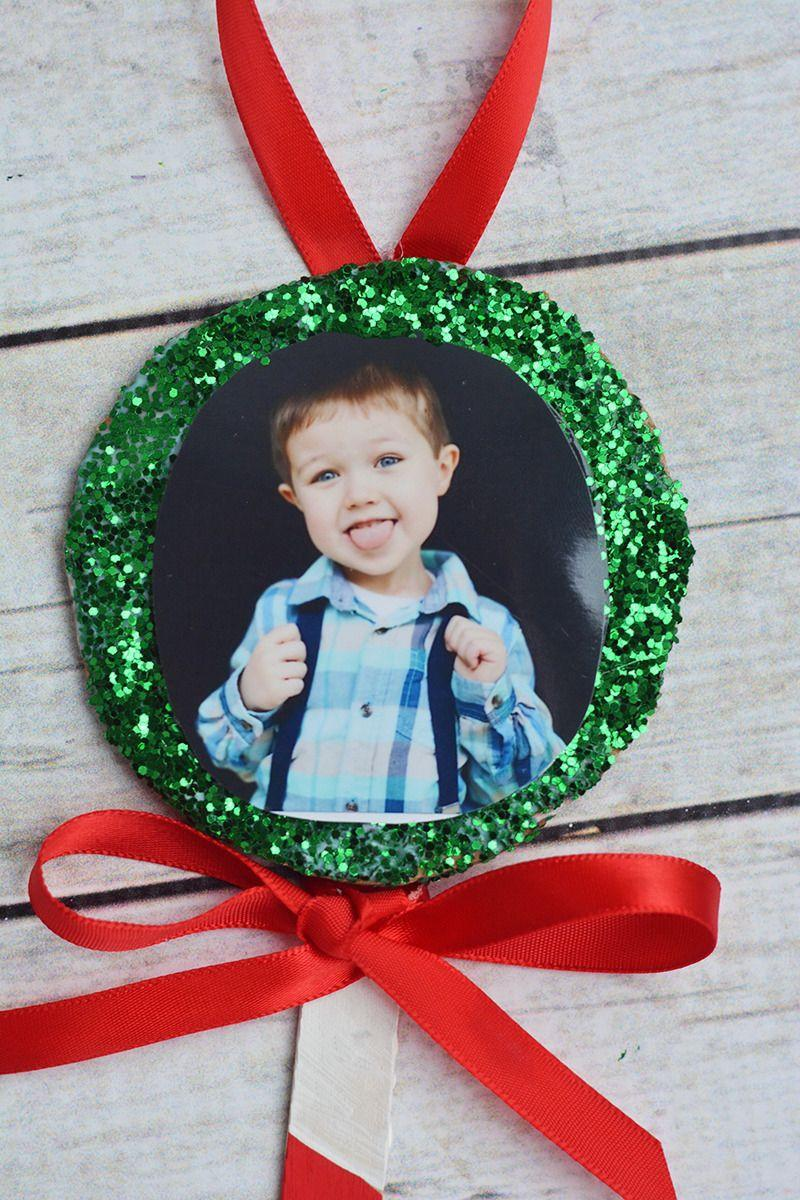 "<p>Paint a popsicle stick and top with ribbon and glittery details. Hang your totally personal and homemade ornaments from your tree, or give as thoughtful gifts for loved ones, customizing each thoughtfully to the recipient's favorite style or color palette.</p><p><em><a href=""https://www.iheartartsncrafts.com/lollipop-photo-ornament-craft-kids/"" rel=""nofollow noopener"" target=""_blank"" data-ylk=""slk:Get the tutorial at I Heart Arts n Crafts»"" class=""link rapid-noclick-resp"">Get the tutorial at I Heart Arts n Crafts»</a></em><br></p>"