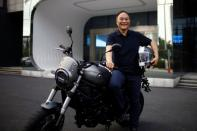 Zhejiang Geely Holding Group's Chairman Li Shufu poses for pictures with a Benelli Leoncino 800 motorcycle at Geely headquarters in Hangzhou