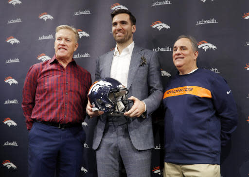Denver Broncos quarterback Joe Flacco, center, holds his new team's helmet as general manager John Elway, left, and head coach Vic Fangio join in for a photograph during a news conference at the NFL football team's headquarters Friday, March 15, 2019, in Englewood, Colo. (AP Photo/David Zalubowski)