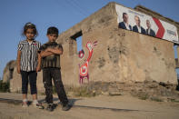 Armenian children look at a photographer standing in front of a damaged building with the posters of parties candidates in Shurnkh village, about 200 km. (125 miles) south-east of Yerevan, Armenia, Tuesday, June 15, 2021. The village was cut in two by a newly defined border with Azerbaijan, and she lost her house in the peace deal. (AP Photo/Areg Balayan)