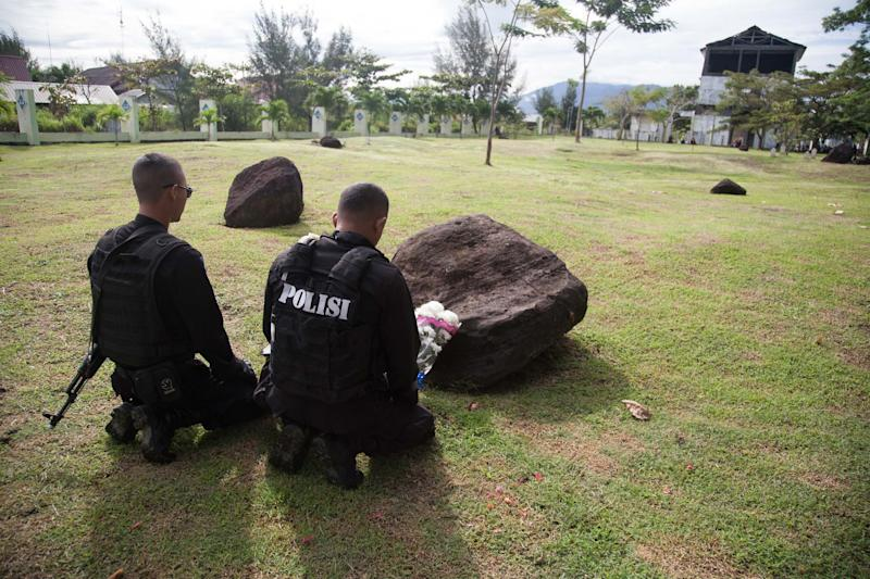 Policemen pray for their dead friends and relatives at a mass grave for victims of the December 26, 2004 tsunami, in Banda Aceh, northern Sumatra, on December 26, 2014 (AFP Photo/Chaideer Mahyuddin)