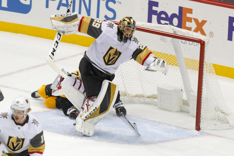 Vegas Golden Knights goaltender Marc-Andre Fleury (29) twists out of the way as Pittsburgh Penguins' Patric Hornqvist slides under him through the goal crease during the first period of an NHL hockey game, Saturday, Oct. 19, 2019, in Pittsburgh. (AP Photo/Keith Srakocic)