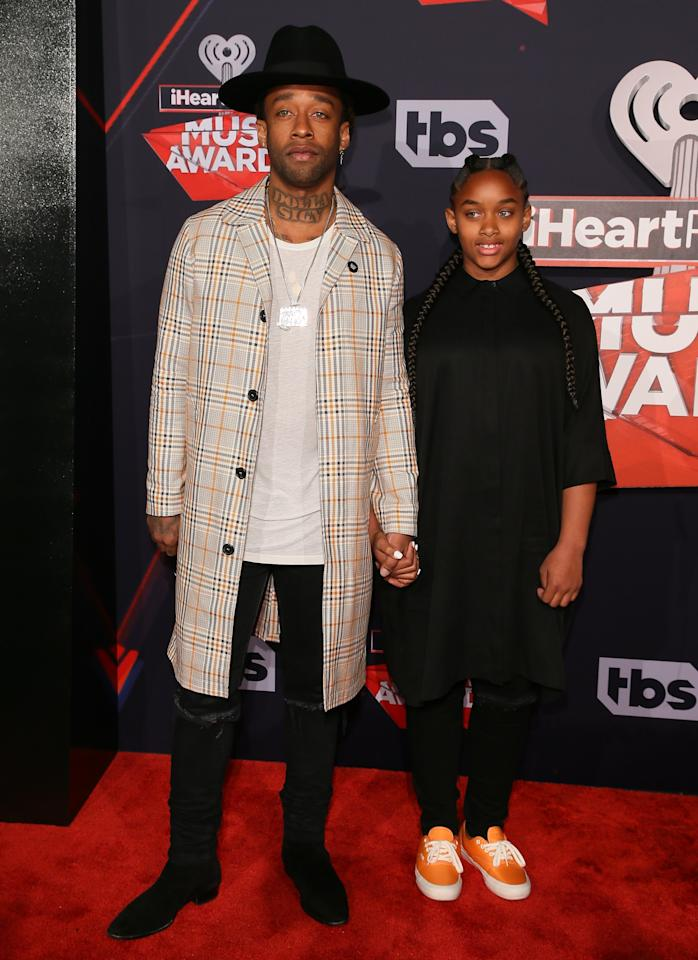 <p>Ty Dolla Sign brought his daughter as his iHeartRadio Awards date and dutifully suited up in some dad outerwear for the occasion. But since he's about a million times cooler than most dads, he wore the tartan coat with ripped jeans and a whole bunch of swaggy accessories.</p>