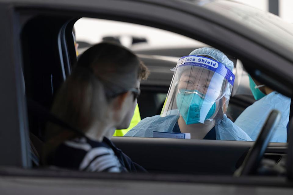 A health care worker speaking to people at a drive-thru Covid testing clinic.