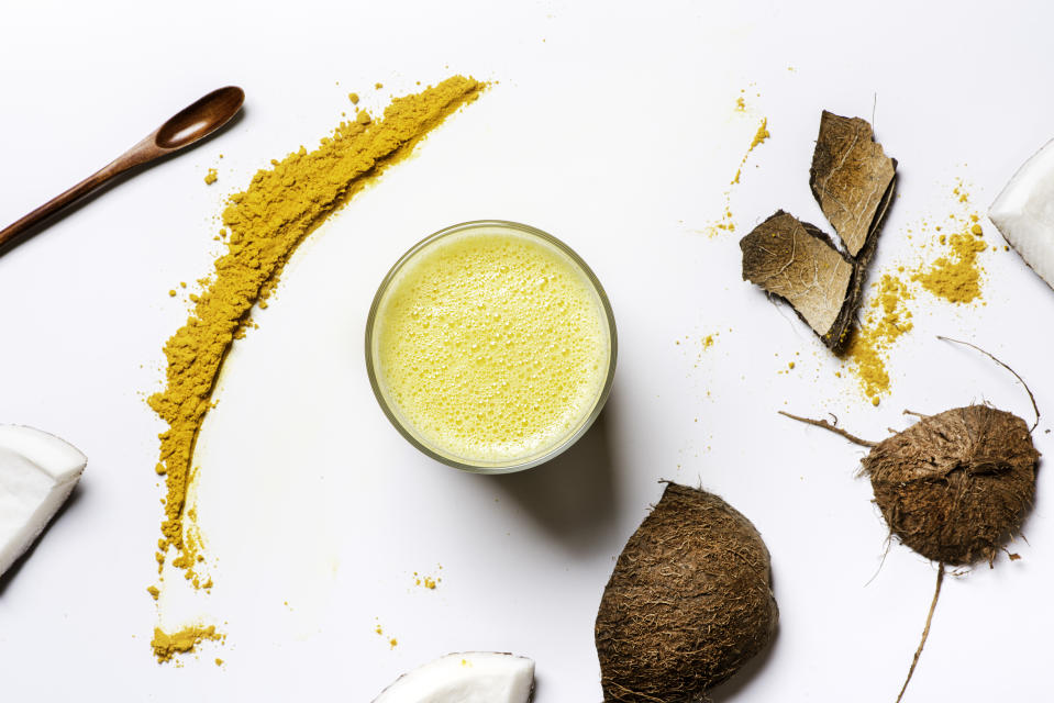 Golden milk. Coconut milk with turmeric, spices and honey in glasses, coconut and turmeric powder on a white background, top view, flat lay. Indian drink haldi ka doodh, vegan food.