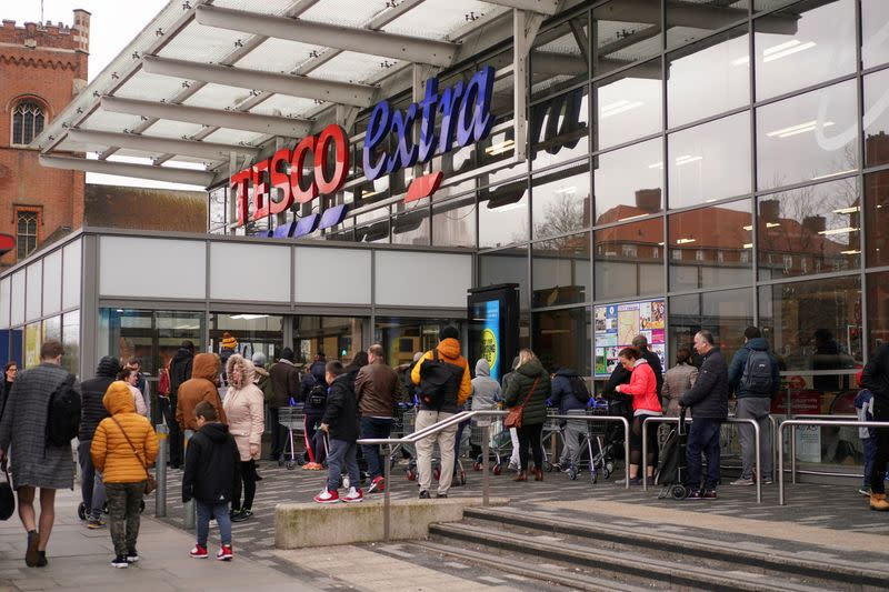 FILE PHOTO: People queue outside of a supermarket before it opens, as the number of coronavirus cases grow around the world, in London