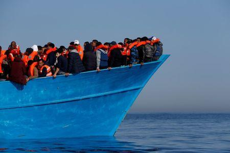 FILE PHOTO: Migrants on a wooden boat await rescue by the Malta-based NGO Migrant Offshore Aid Station (MOAS) in the central Mediterranean in international waters off the coast of Sabratha in Libya, April 15, 2017. REUTERS/Darrin Zammit Lupi/File Photo