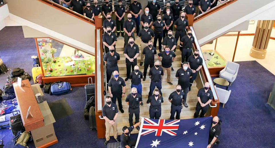 A photo of firefighters at their pre-deployment briefing before flying to Canada. The group poses on a stairway as two firefighters hold an Australian flag at the front. Source: NSW Rural Fire Service