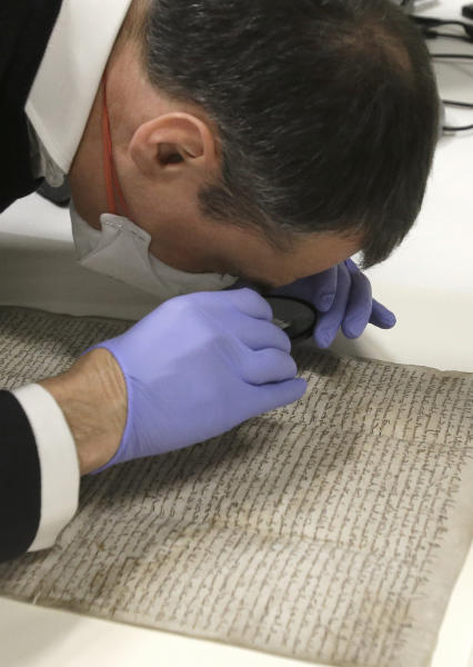 In this Wednesday, Feb. 5, 2014 photo, wearing special gloves and a mask, Chris Woods, director of London's National Conservation Service, uses a magnifying glass to inspect the Magna Carta, after its arrival in Houston. The centuries old parchment, which has never left England before, will be on display at the Houston Museum of Natural Science for six months starting Feb. 14, 2014. (AP Photo/Pat Sullivan)