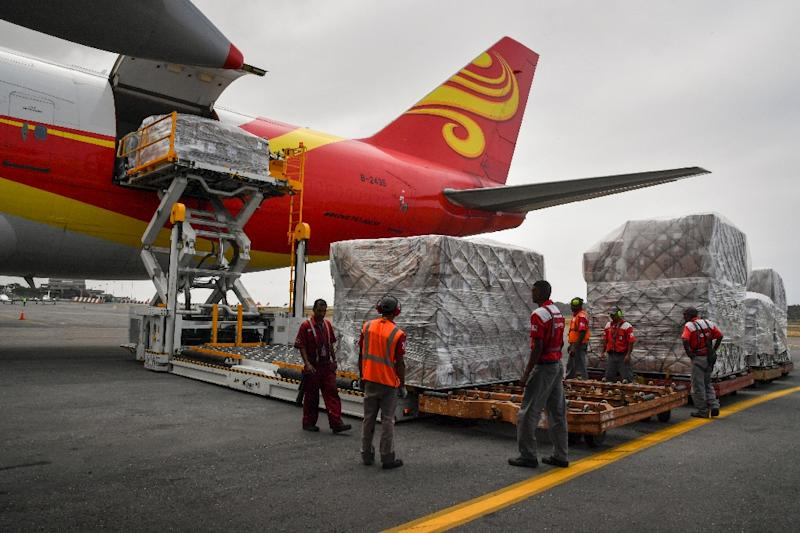Workers unload medicines and disposable medical supplies from a Chinese 747 cargo plane after it landed at Simon Bolivar International Airport on March 29, 2019 (AFP Photo/Yuri CORTEZ)