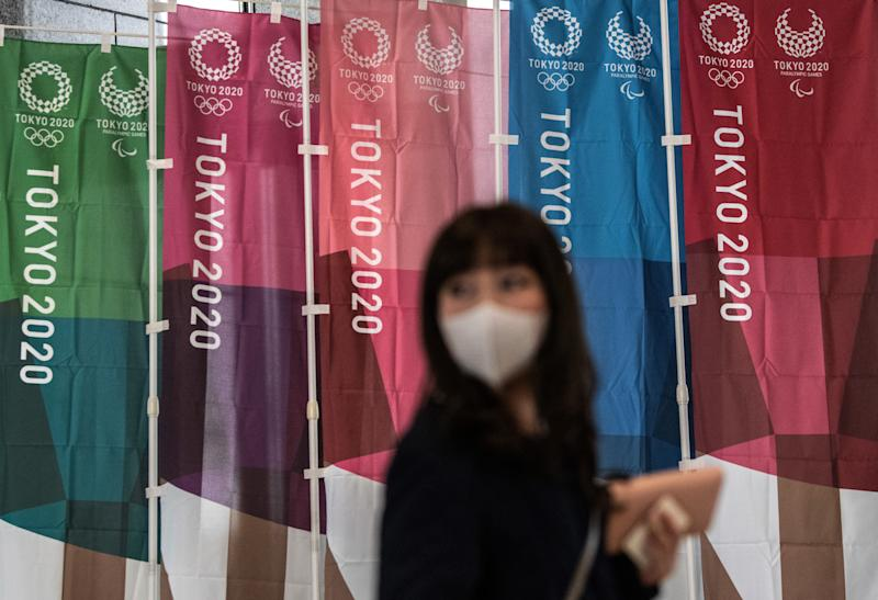TOKYO, JAPAN - MARCH 19: A woman walks past Tokyo 2020 Olympics banners on March 19, 2020 in Tokyo, Japan. As Japanese and IOC officials continued to insist that the Games would go ahead as planned, Japans Deputy Prime Minister said on Wednesday that the Tokyo Olympics are cursed, as speculation grows that the Olympics will have to be postponed due to the ongoing coronavirus (COVID-19) pandemic. (Photo by Carl Court/Getty Images)