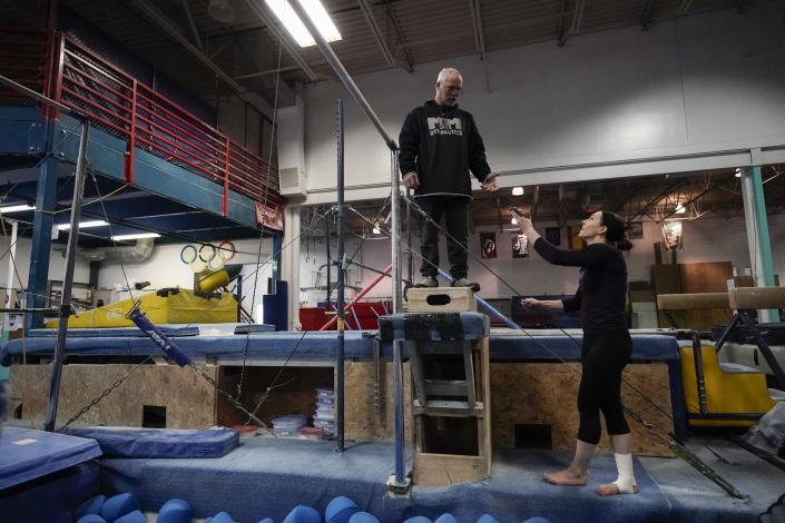 Former gymnastics world champion and Olympic silver medalist Chellsie Memmel works out with her father and coach Andy Memmel Thursday, Feb. 18, 2021, in New Berlin, Wisc. Memmel, 32, rediscovered her love for the sport, so much so the married mother of two is making an unlikely comeback. (AP Photo/Morry Gash)