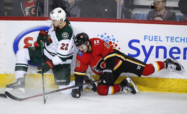 Minnesota Wild's Nino Niederreiter, left, of Switzerland, is checked by Calgary Flames' Derek Ryan during second-period NHL hockey game action in Calgary, Alberta, Thursday, Dec. 6, 2018. (Jeff McIntosh/The Canadian Press via AP)