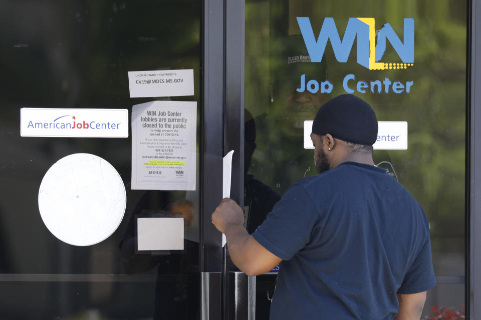 Tyrone Keoton Jr., is handed an unemployment benefit application form by a security guard behind the glass doors of this state WIN Job Center in north Jackson, Miss., Thursday, April 2, 2020. The job centers lobbies are closed statewide to prevent the spread of COVID-19. The agency encourages residents to apply for their benefits on line, however, the system has been stressed by the large numbers of applicants. The local job centers are making paper unemployment applications available and applicants are filling them out and pushing them back through the mail slots or doors as well as they can. (AP Photo/Rogelio V. Solis)