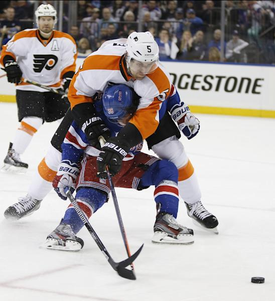 Philadelphia Flyers defenseman Braydon Coburn (5) smothers New York Rangers right wing Mats Zuccarello (36), of Norway, in the second period of Game 2 of the first round of the Stanley Cup hockey playoffs at Madison Square Garden in New York, Sunday, April 20, 2014. Coburn was called for holding. (AP Photo/Kathy Willens)