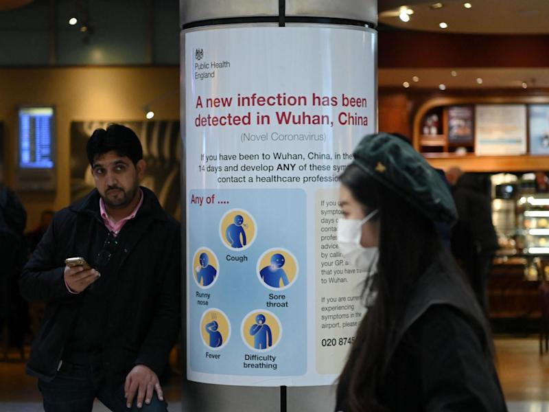 A woman wearing a face mask passes a Public Health England sign at London Heathrow Airport, the busiest airport in Europe, on 28 January 2020: Daniel Leal-OlivasAFP via Getty Images