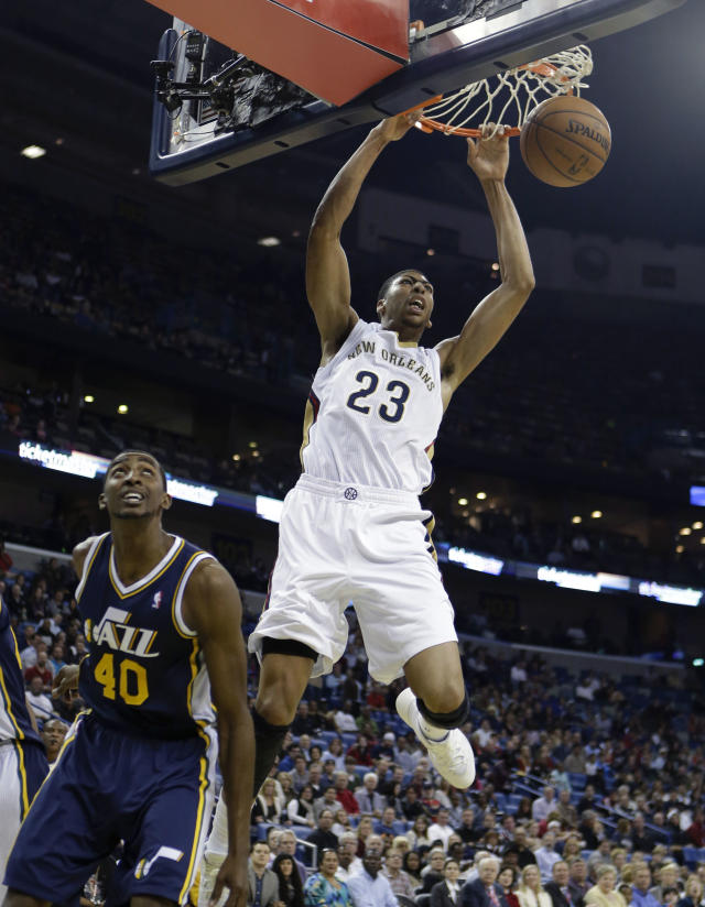 New Orleans Pelicans power forward Anthony Davis (23) slam-dunks over Utah Jazz small forward Jeremy Evans (40) in the first half of an NBA basketball game in New Orleans, Wednesday, Nov. 20, 2013. (AP Photo/Gerald Herbert)