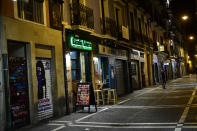 A person walks along the unusually deserted Saint Nicolas street, to prevent the spread of coronavirus, in Pamplona, northern Spain, Friday, March 13, 2020. For most people, the new COVID-19 coronavirus causes only mild or moderate symptoms, such as fever and cough, but for some, especially older adults and people with existing health problems, it can cause more severe illness, including pneumonia. (AP Photo/Alvaro Barrientos)