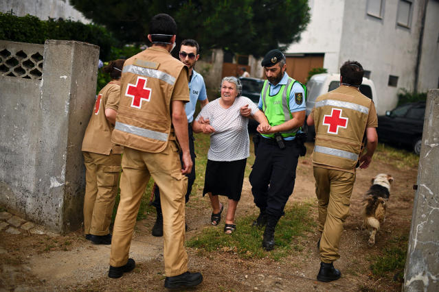 <p>People are evacuated from their houses by Red Cross and police due the proximity of a dangerous wildfire at Torgal, Castanheira de Pera, Portugal, June 18, 2017. (Patricia De Melo Moreira/AFP/Getty Images) </p>