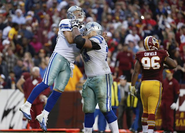 Dallas Cowboys quarterback Tony Romo, left, is hugged by guard Mackenzy Bernadeau as Washington Redskins nose tackle Barry Cofield, right, walks off the field after Romo threw the game tying touchdown pass late in the fourth quarter of an NFL football game in Landover, Md., Sunday, Dec. 22, 2013. The Cowboys defeated the Redskins 24-23. (AP Photo/Alex Brandon)