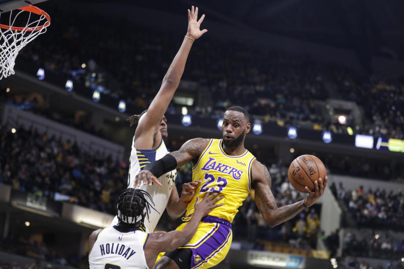 Los Angeles Lakers forward LeBron James (23) makes a pass as he's defended by Indiana Pacers guard Aaron Holiday (3) and center Myles Turner (33) during the first half of an NBA basketball game in Indianapolis, Tuesday, Dec. 17, 2019. (AP Photo/Michael Conroy)