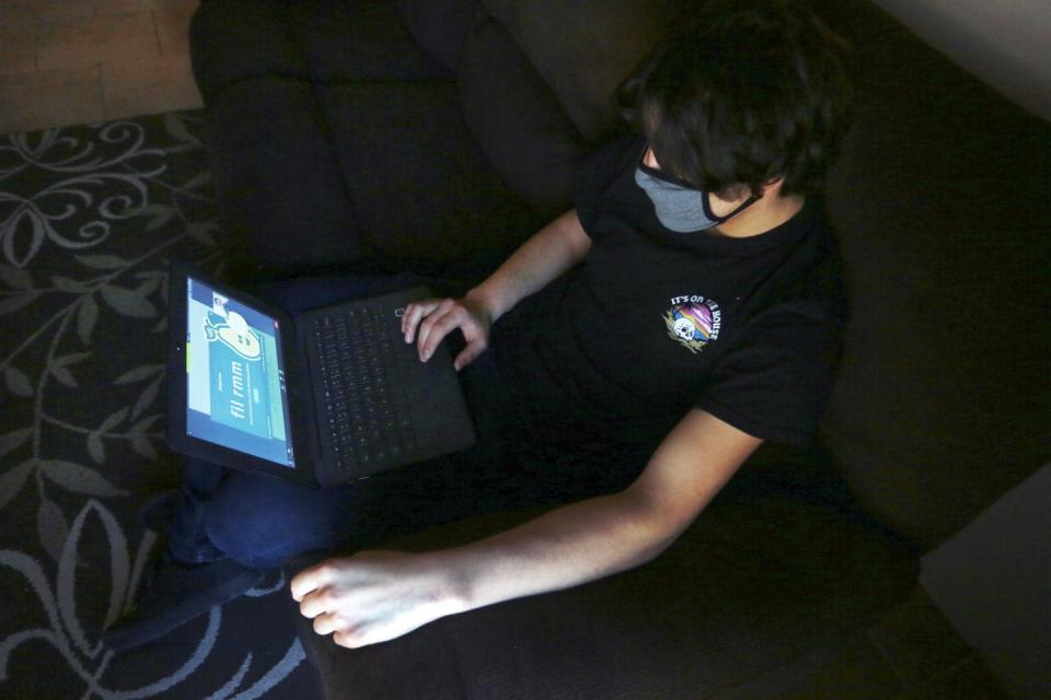 A young student wearing a mask uses a laptop