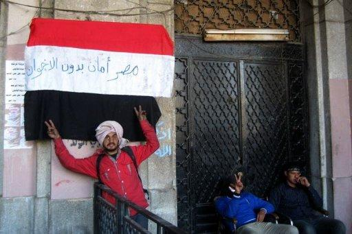 """<p>An Egyptian protester flashes the sign of victory in front a national flag on which is written in Arabic """"Egypt is moor safe without Muslim Brotherhoods'' in front of the Mugamma, Cairo's main administrative building on February 24, 2013. In Cairo on Sunday, protesters blocked the doors to the main administrative building as part of a growing campaign of civil disobedience around the country</p>"""