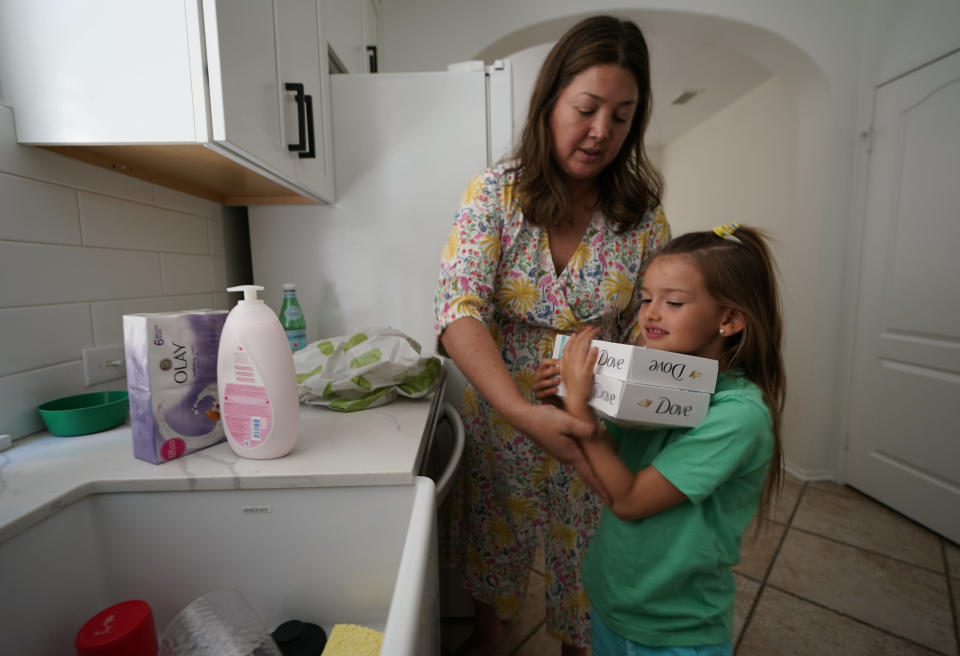 In this Wednesday, July 21, 2021, photo, Attorney Cynthia Carrasco White and her daughter, Charlotte, 6 unpack supplies delivered by Instacart at their home in the Porter Ranch area of Los Angeles. Carrasco White, a single mother and a lawyer for a Los Angeles nonprofit, used to think delivery was a luxury she couldn't afford. But she started getting meals, groceries and other necessities delivered last year so she could avoid taking her young, unvaccinated daughters to the store. Carrasco White has come to see delivery as a lifeline that saves her time, gas money and child care expenses. She uses various apps, including Uber Eats and DoorDash, and takes advantage of deals when she can. (AP Photo/Damian Dovarganes)