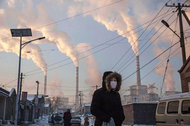 PHOTO: A woman wears a mask while walking in a neighborhood next to a coal fired power plant on Nov. 26, 2015, in Shanxi, China. (Kevin Frayer/Getty Images, FILE)