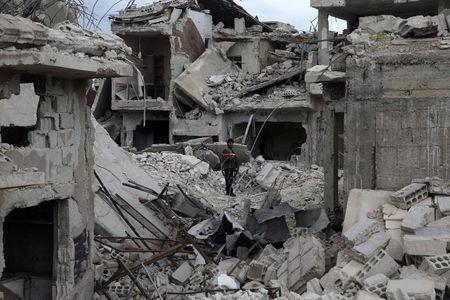 A man stands on rubble of damaged buildings in the besieged town of Douma