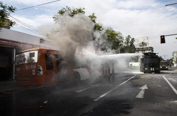 A police water cannon extinguishes a burning bus that was set alight by demonstrators during a protest in Santiago, Chile, Saturday, Oct. 19, 2019. The protests started on Friday afternoon when high school students flooded subway stations, jumping turnstiles, dodging fares and vandalizing stations as part of protests against a fare hike, but by nightfall had extended throughout Santiago with students setting up barricades and fires at the entrances to subway stations, forcing President Sebastian Pinera to announce a state of emergency and deploy the armed forces into the streets. (Photo: Esteban Felix/AP)