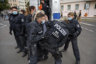 Police restrain a demonstrator, during a protest against coronavirus restrictions, in Berlin, Saturday, Aug. 28, 2021. (Christophe Gateau/dpa via AP)