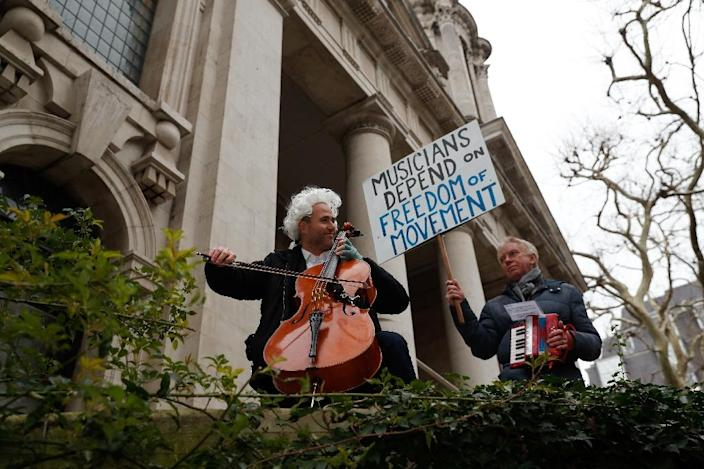 """The family of British-German musician Simon Wallfisch, seen on the cello during a London performance to protest Brexit, were persecuted by the Nazis, but along with hundreds of others he is taking a German passport """"to shore up some security for my future"""" (AFP Photo/Adrian DENNIS)"""