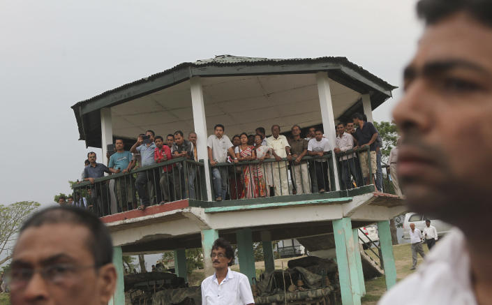 People watch as Indian wildlife officials prepare to fly an unmanned aircraft or drone at the Kaziranga National Park at Kaziranga in Assam state, India, Monday, April 8, 2013.Wildlife authorities used drones on Monday for aerial surveillance of the sprawling natural game park in northeastern India to protect the one-horned rhinoceros from armed poachers. The drones will be flown at regular intervals to prevent rampant poaching in the park located in the remote Indian state of Assam. The drones are equipped with cameras and will be monitored by security guards, who find it difficult to guard the whole 480-square kilometer (185-square mile) reserve. (AP Photo/Anupam Nath)