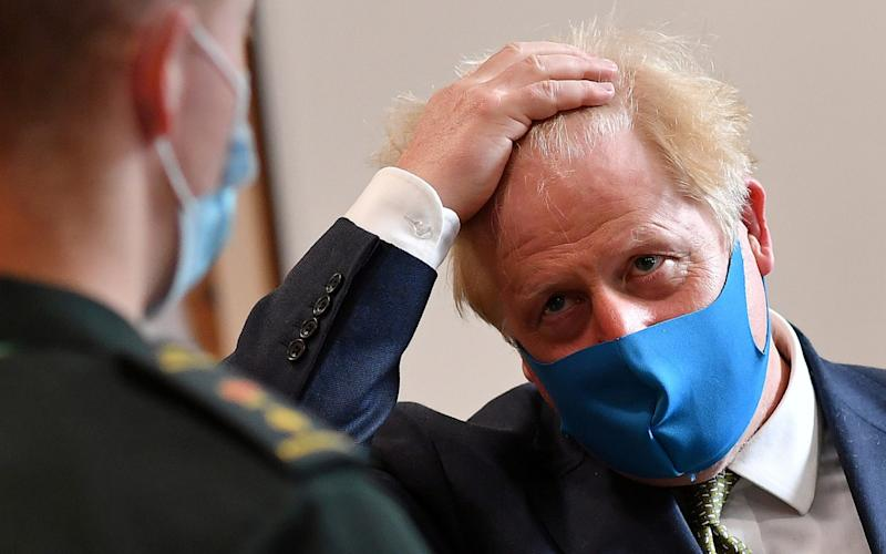 Boris Johnson wears a face mask as he he visits the London Ambulance Service NHS Trust in London - Reuters