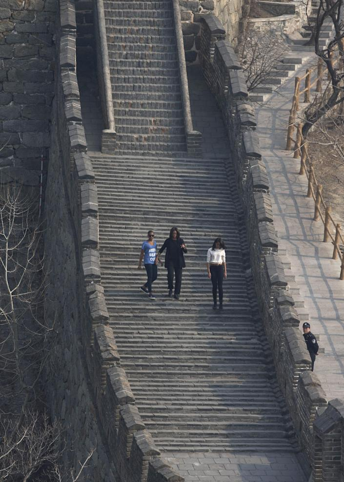 U.S. first lady Michelle Obama walks with her daughters Malia, right, and Sasha, left, as they climb the steps at the Mutianyu section of the Great Wall of China in Beijing Sunday, March 23, 2014. (AP Photo/Andy Wong)