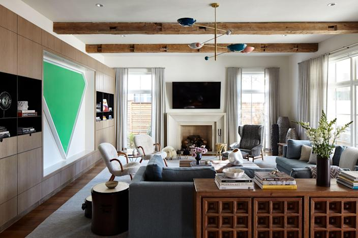 """In the family room, in which cabinetry was custom designed to fit a triangular painting by Ellsworth Kelly titled <em>Green Panel</em>, a large square sectional from <a href=""""https://www.dmitriyco.com"""" rel=""""nofollow noopener"""" target=""""_blank"""" data-ylk=""""slk:Dmitriy & Co"""" class=""""link rapid-noclick-resp"""">Dmitriy & Co</a>. sits behind a 1960s Spanish console from <a href=""""https://www.morentz.com"""" rel=""""nofollow noopener"""" target=""""_blank"""" data-ylk=""""slk:Morentz"""" class=""""link rapid-noclick-resp"""">Morentz</a>. """"It was a beautiful find,"""" says Liss. """"It really works with the rustic beams and balances the modern nature of the millwork."""""""
